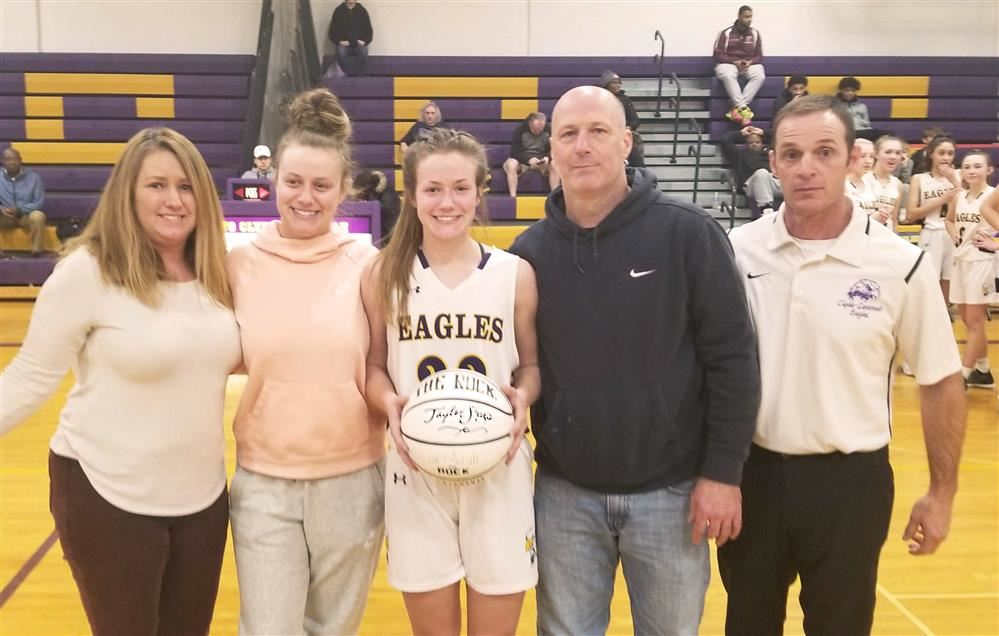 Tayler Sharp receives a commemorative basketball for scoring her 1000th point