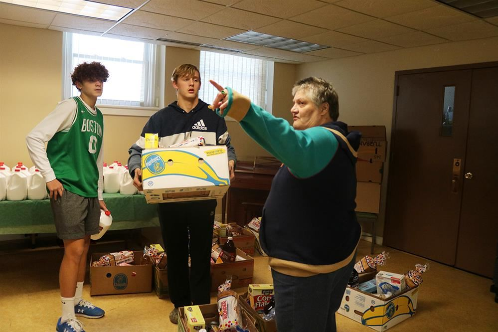 Clyde-Savannah basketball players assist a community member at the food drive.